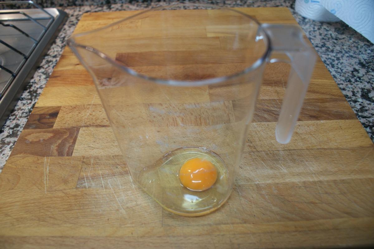 Introduce un huevo en el recipiente